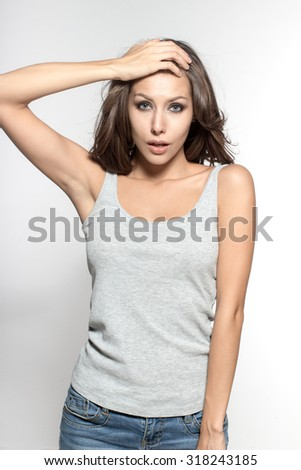 Awesome Caucasian attractive joyful happy sexy female model with brunette hair is grimacing in studio, wearing gray sleeveless shirt, isolated on white background - stock photo