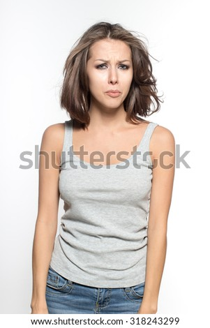 Awesome Caucasian attractive sad female model with brunette hair is grimacing in studio, wearing grey sleeveless shirt, isolated on white background - stock photo