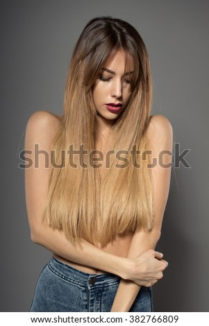 Awesome caucasian attractive sexy fashion model with extended hair posing in studio topless, perfect make up, tanned skin, isolated on grey background, retouched image - stock photo