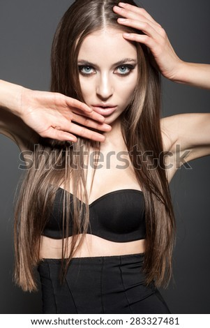 Awesome caucasian attractive sexy fashion model with long brunette natural hair, beautiful eyes, full lips, perfect skin posing  in studio, touching face, beauty photo shoot, retouched image - stock photo