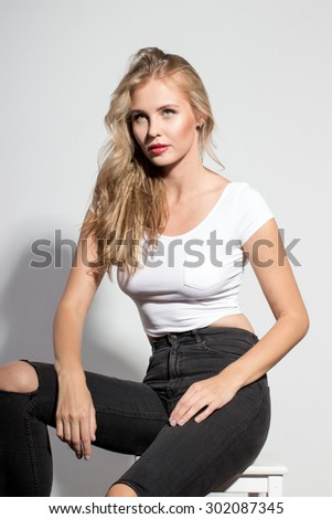 Awesome caucasian attractive sexy professional female model with blond hair posing in studio wearing white shirt and black ragged jeans, sitting on chair, isolated on white background - stock photo