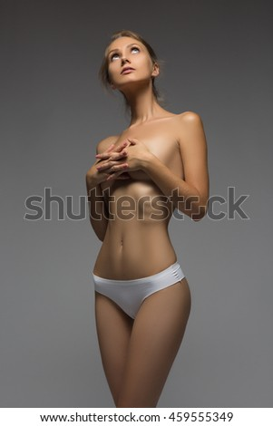 Awesome caucasian attractive sexy professional female model with brunette hair posing in studio topless, perfect make up, isolated on gray - stock photo