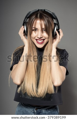 Awesome caucasian attractive sexy professional female model with long hair posing in studio wearing black shirt and wireless headphones, isolated on grey background - stock photo