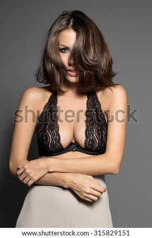 Awesome Caucasian attractive shy sexy female model with brunette hair posing in studio, wearing black transparent lingerie, isolated on gray background - stock photo