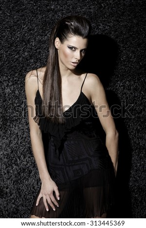 Awesome caucasian fashion model with stylish hairstyle, long legs, full lips, perfect skin, wearing transparent cocktail dress, standing near shiny black carpet, beauty photoshoot, retouched image - stock photo