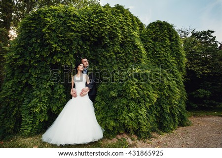Awesome couple watching on mysterious castle from the beautiful garden - stock photo