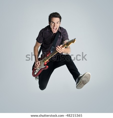 Awesome guitar player jumps with passion in studio - stock photo