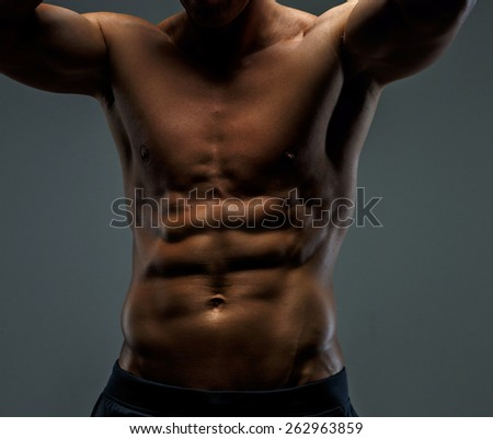 Awesome muscular male body in black shorts. Isolated on grey background. - stock photo