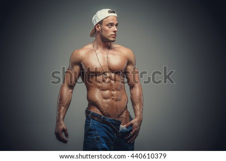 Awesome muscular shirtless male in a jeans and white cap isolated on a grey background. - stock photo