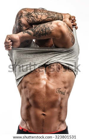 Awesome muscular tattooed man putting out his shirt. Isolated on white background. - stock photo