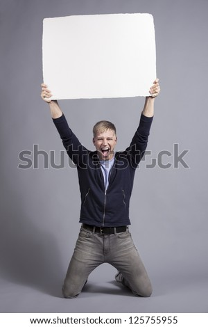 Awesome news: Excited laughing man holding up white blank panel with space for text isolated on grey background. - stock photo