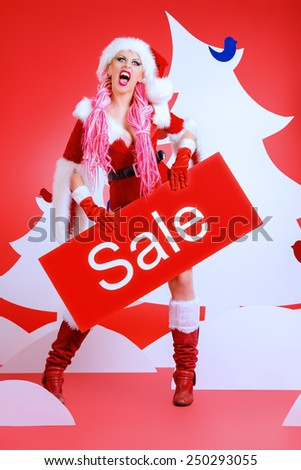 Awesome sexual Christmas babe alluring with sale board in Christmas decorations, red background. Christmas sale. Shopping. Full length portrait. - stock photo