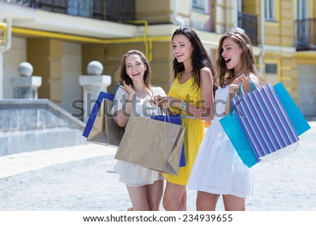 Awesome shopping sales proposition. Three young and attractive women are standing on the street with shopping bags. Girls are smiling and looking forward happily, because of their purchases - stock photo