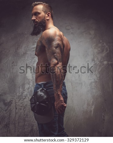 Awesome tattooed bearded man with naked torso posing over grey background.
