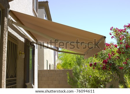 Awning above back yard door to residential two-storied house - stock photo