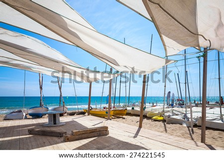 Awnings in sails shape covering relax area near sailing boats on the sandy beach in Calafell town, coast of Mediterranean sea, Catalonia, Spain - stock photo