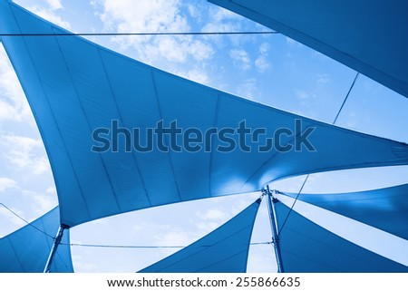 Awnings in sails shape over cloudy sky background. Blue toned photo - stock photo