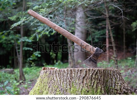 ax carved in stump in forest - stock photo