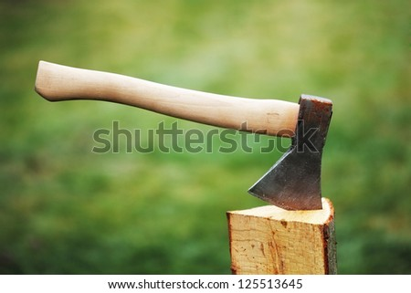 Ax in a log on the background of green grass - stock photo