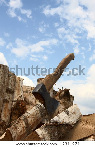 Axe and logs on a background of the sky - stock photo