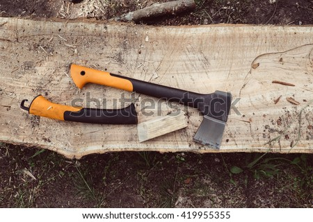 Axe and saw on wood. Woodworking tool and wooden background. Axe in wood, chopping timber. Lumberjack axe in wood. Big forest axe on wood background. Travel, adventure, camping gear, outdoors items. - stock photo