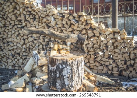 Axe Cut into Wood after Chopping Firewood against stack of wood near rusty metal fence Rural scene  - stock photo