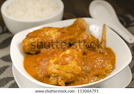 Ayam Kari Kapitan - Malaysian spicy chicken curry with coconut milk served with sticky rice. Traditional Nyonya cuisine. Low key lighting. Close up. - stock photo