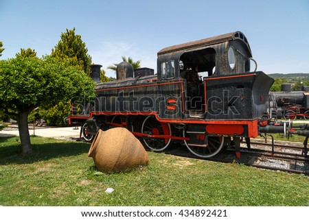 AYDIN, TURKEY - APRIL 30, 2016 : View of historical old iron train locomotives exhibited in Camlik Train Museum, on blue sky background.