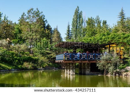AYDIN, TURKEY - MAY 1, 2016 : Landscape view of natural park with lake, trees and wooden arbour on bright blue sky background. - stock photo