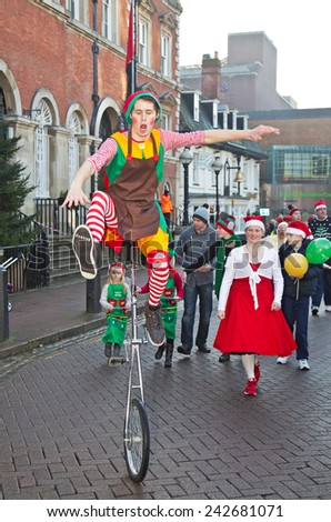 AYLESBURY, UK - NOVEMBER 30: A unicyclist performer parades through the market square in Aylesbury along with other carnival acts as part of the Christmas festivities on November 30, 2014 in Aylesbury