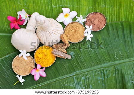 Ayurveda pads with powders, flowers on banana leaves . top view  - stock photo