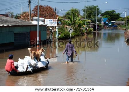 AYUTTAYA,THAILAND - NOVEMBER 13: People floating their belongings while wading through deep water during the monsoon flooding of November 13, 2011 in Ayuttaya, Thailand. - stock photo