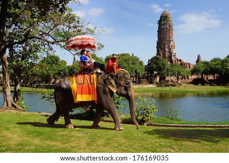 AYUTTHAYA, THAILAND - DECEMBER 17: Tourists on an elefant ride around the Park on December 17, 2013 in Ajutthaja,Thailand.The city of Ayutthaya was founded in 1350 and was the capital of the country.  - stock photo