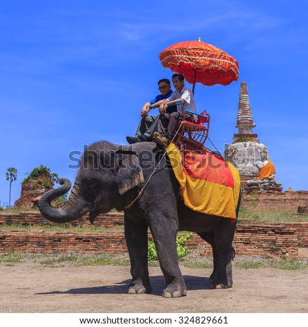AYUTTHAYA, THAILAND - JUNE 1 : Tourists on an elephant ride tour of the ancient city Ayutthaya a visit to the historic site and behind is the Wat Chang Temple on June 1, 2015 in Ayutthaya Thailand