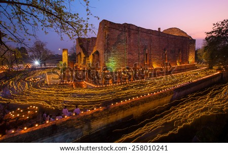 AYUTTHAYA ,THAILAND - MARCH 4, 2015 : Old temple walking with lighted candles in hand around a temple candle light trail of Buddhism Ceremony at temple ruin on Magha Puja Day thailand - stock photo