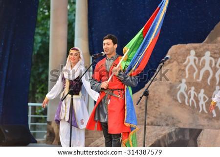 AZERBAIJAN, MASALLI, JUNE 13, 2014: Azerbaijan international folk festival 2014 in Masalli city. Azerbaijan dancers carries flag. - stock photo