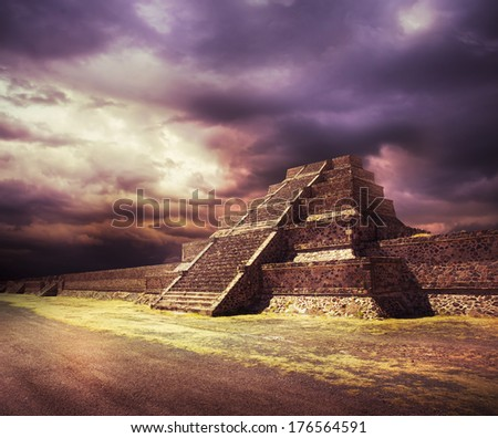Aztec pyramid at sunset with dramatic sky, Not a real place, just a representation of ancient Mexico using parts of an actual pyramid to make the composite - stock photo