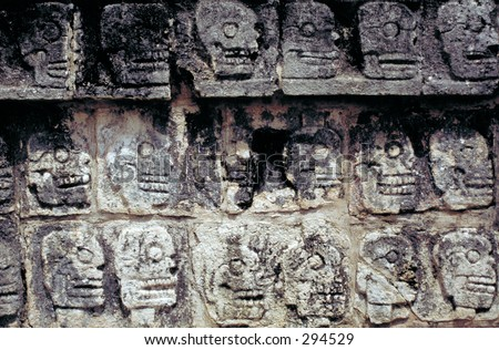 Aztec sacrificial altar with carved stone skull reliefs, Chichen Itza, Mexico - stock photo