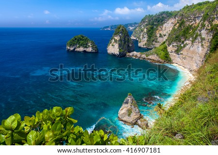 Azure beach with rocky mountains and clear water of Indian ocean at sunny day / A view of a cliff in Bali Indonesia / Bali, Indonesia - stock photo