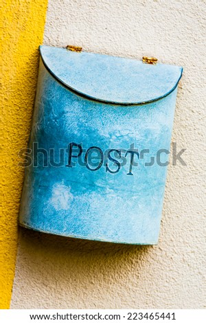 Azure blue painted old metal mailbox on yellow and white wall - stock photo