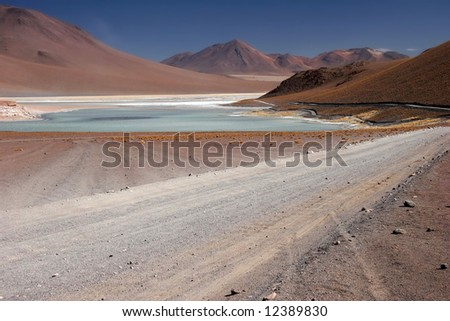 Azure clear sky over the mountain range with lake and country road leading cross mountains. Altiplano. Bolivia. Bolivia-Chilean border - stock photo