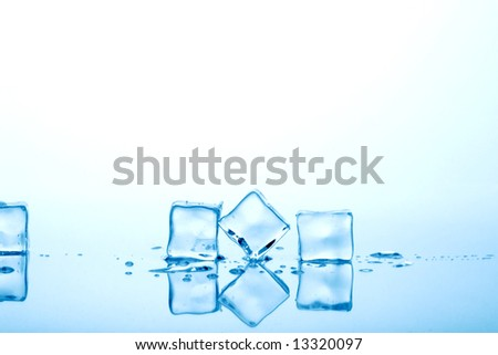 Azure colored ice cubes melted in water on reflection surface ready to be added to a cocktail - stock photo