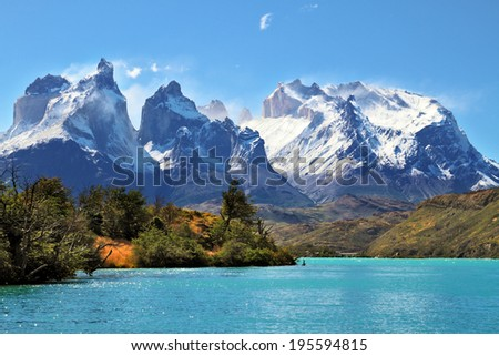 Azure Lake Pehoe at the foot of the magnificent snow-covered cliffs of Los Kuernos. National Park Torres del Paine, Chile - stock photo