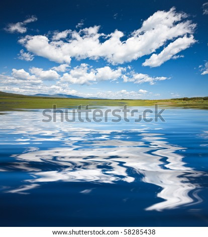 azure lake with a reflection of the clouds of heaven at the foot of the mountains - stock photo
