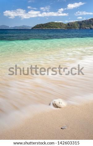 azure sea washes the white pebble on a sandy beach - stock photo