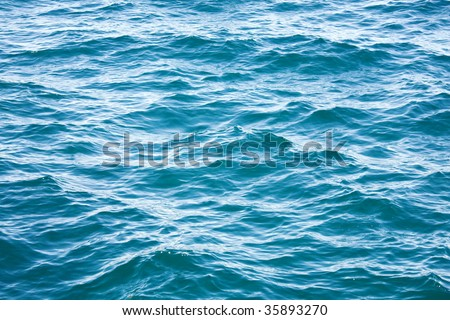 Azure sea water surface with ripple and cloud reflections - stock photo