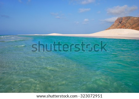 Azure water and white sand dune. A sandy coastline and a colorful lone cliff at the sunset. Qalansiya beach in the lagoon Detwah , Socotra island, Yemen - stock photo