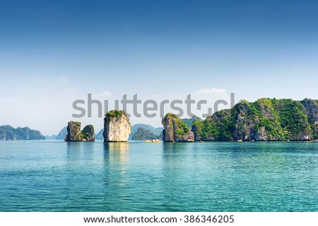 Azure water of the Ha Long Bay at the Gulf of Tonkin of the South China Sea, Vietnam. Scenic view of blue lagoon and karst towers-isles. The Halong Bay is a popular tourist destination of Asia. - stock photo