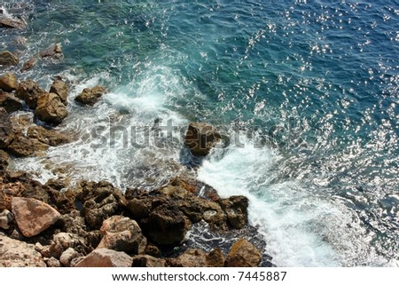 Azure wave encountering rocky obstacle breaks creating foam and a lot of droplets and retreats. - stock photo