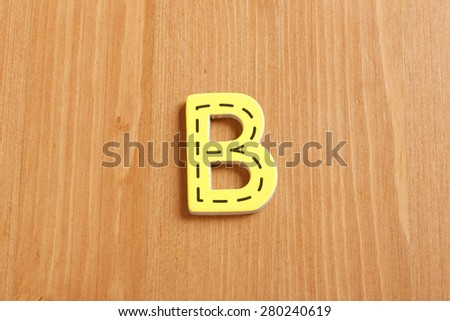 B, spell by woody puzzle letters with woody background - stock photo